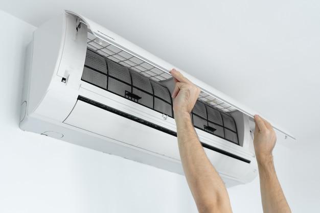 Facet czyści filtr domowego klimatyzatora z kurzu.