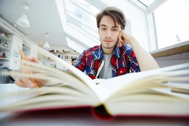 Facet czyta w bibliotece