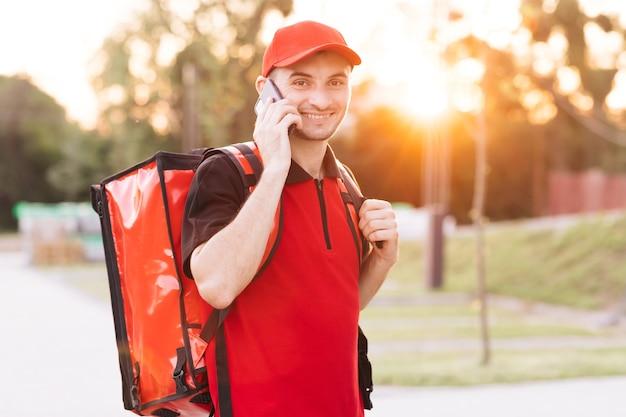 Facet dostarczający jedzenie z czerwonym plecakiem dostarcza zamówienia męskiego kuriera z izotermicznym pudełkiem na żywność