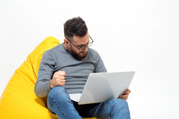 Facet frustruje siedząc na żółtym pufowym krześle