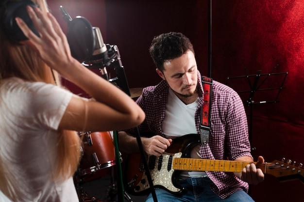 Facet gra na gitarze elektrycznej i śpiewa kobieta