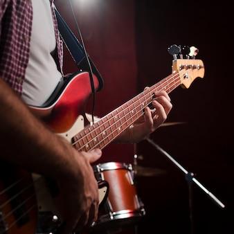 Facet gra na gitarze elektrycznej i stoi