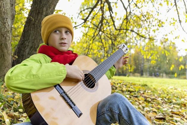 Facet gra na gitarze w jesiennym parku dziecko uczy się grać na gitarze akustycznej na świeżym powietrzu jesienna melancholia