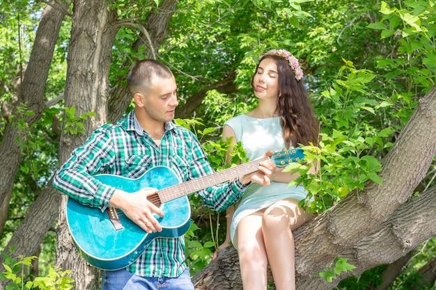 Facet gra na swojej ukochanej gitarze. dziewczyna z przyjemnością z zamkniętymi oczami słucha siedząc na drzewie