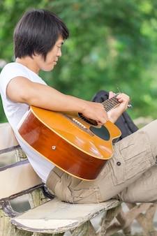 Facet grający na gitarze, outdoor, spodnie cargo