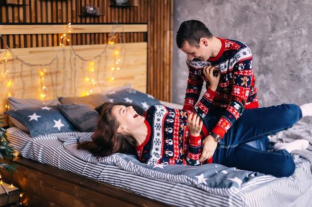 Facet i dziewczyna bawią się w łóżku. przytulny pokój ozdobiony girlandami.