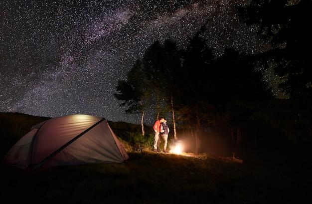 Facet i dziewczyna całują się przy ognisku pod jasnym, gwiaździstym niebem widocznym mleczną drogą w pobliżu namiotu i drzew. romantyczny wieczór na kempingu w lesie.