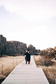 Facet i dziewczyna idą drogą przez uskok silfra w dolinie tingvedlir
