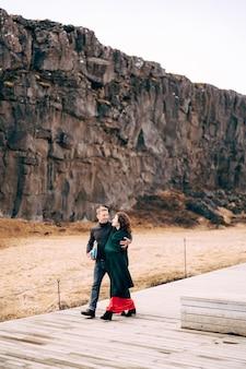 Facet i dziewczyna idą drogą w uskoku silfra w dolinie tingvedlir