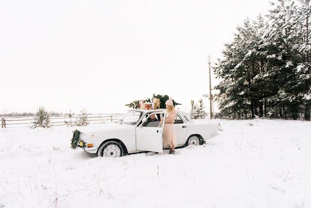 Facet i dziewczyna jeżdżą retro samochodem ozdobionym choinką i prezentami w śnieżnym lesie. koncepcja zimowej świątecznej historii miłosnej