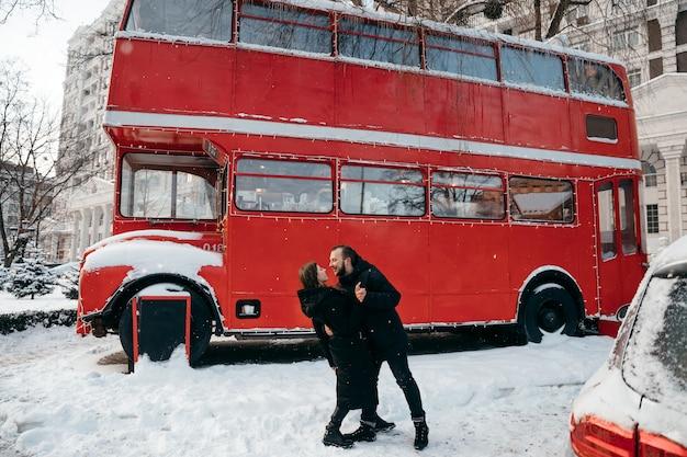 Facet i dziewczyna kochanków całują się na tle czerwonego autobusu