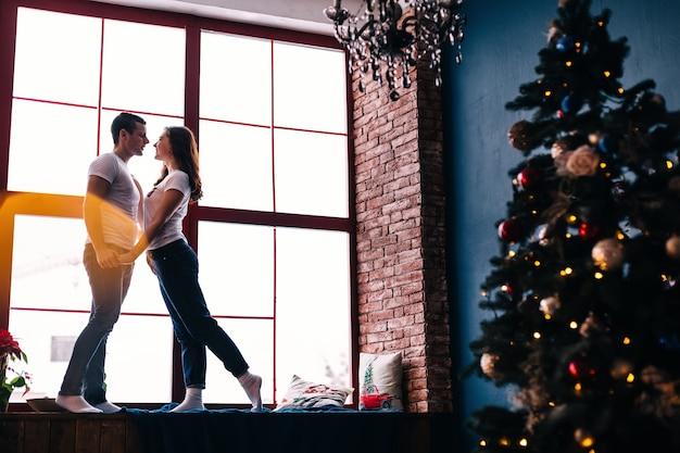 Facet i dziewczyna na parapecie trzymają się za ręce i patrzą na siebie