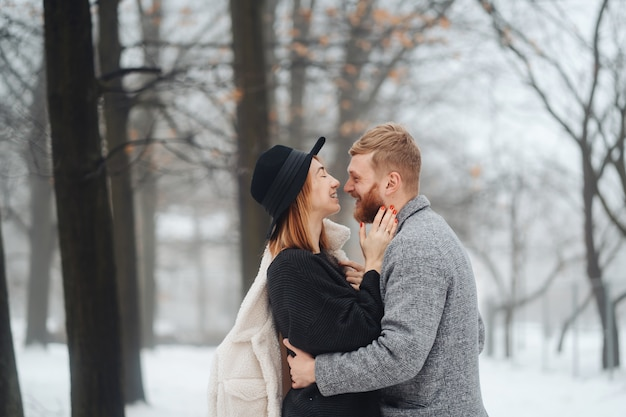 Facet i dziewczyna odpoczywają w zimowym lesie.