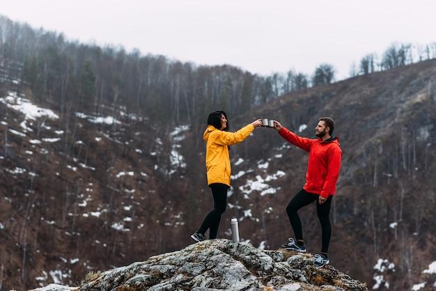 Facet i dziewczyna podróżują w górach. mężczyzna i kobieta piją gorącą herbatę w górach. zakochana para wygrzewa się w gorącej herbacie. wspinaczka górska