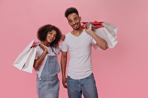 Facet i dziewczyna pozują z torbami na zakupy na różowej ścianie