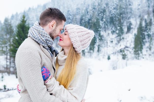 Facet i dziewczyna przytulają się i patrzą na siebie. urocza zima w górach