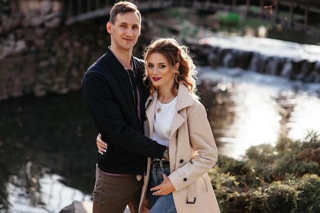 Facet i dziewczyna przytulają się na tle rzeki