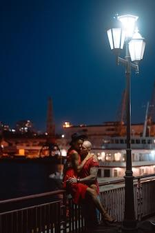 Facet i dziewczyna przytulanie siebie na tle portu w nocy