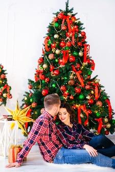 Facet i dziewczyna siedzą na podłodze w pobliżu choinki. facet chce pocałować dziewczynę w czoło i zamknęła oczy
