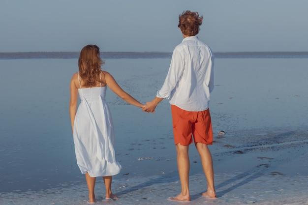 Facet i dziewczyna trzymają się za ręce i patrzą w dal