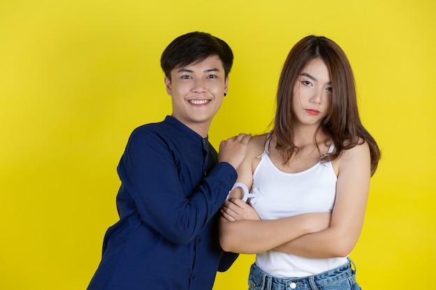 Facet i dziewczyna trzymają symbol mężczyzny i kobiety na żółtej ścianie