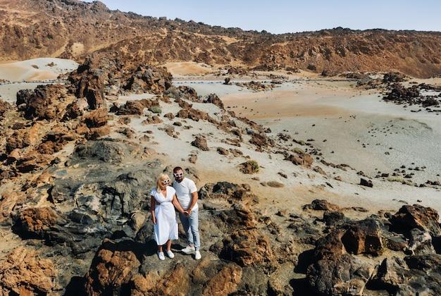 Facet i dziewczyna w białych ubraniach i okularach stoją w kraterze wulkanu el teide, para stoi na górze w kraterze wulkanu na teneryfie w hiszpanii.