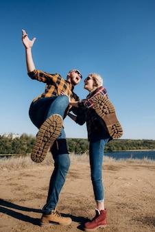 Facet i dziewczyna w koszuli w klatce i butach trekkingowych na granitowych skałach