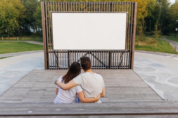 Facet i dziewczyna w parku w kinie na świeżym powietrzu