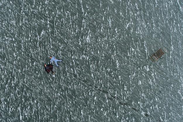 Facet i dziewczyna w piżamach leżą na lodzie zamarzniętego jeziora