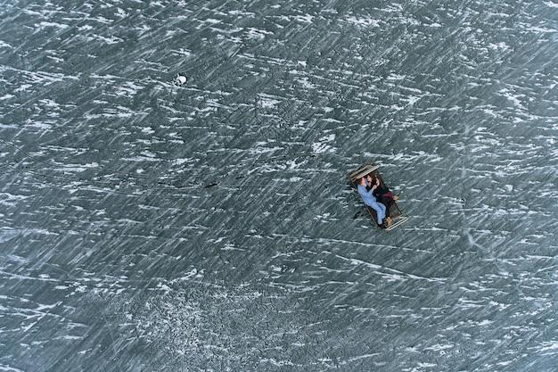 Facet i dziewczyna w piżamach leżą na żelaznym łóżku na lodzie zamarzniętego jeziora