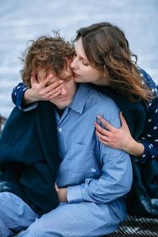 Facet i dziewczyna w piżamach na lodzie zamarzniętego jeziora