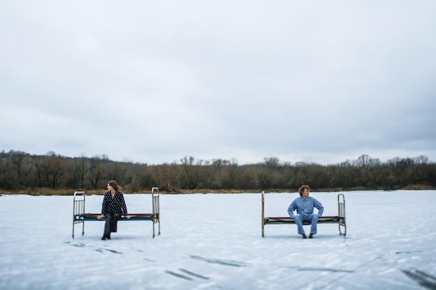 Facet i dziewczyna w piżamach są na lodzie zamarzniętego jeziora