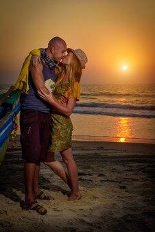 Facet i dziewczyna w pobliżu starej drewnianej łodzi na wybrzeżu oceanu.