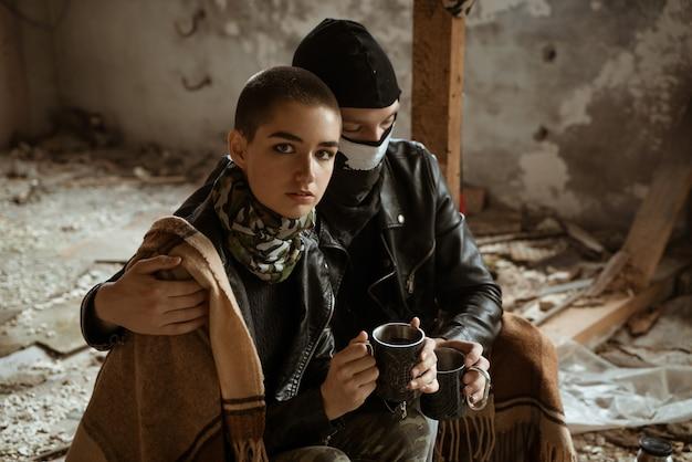 Facet i dziewczyna w slumsach siedzą razem, romans apokalipsy