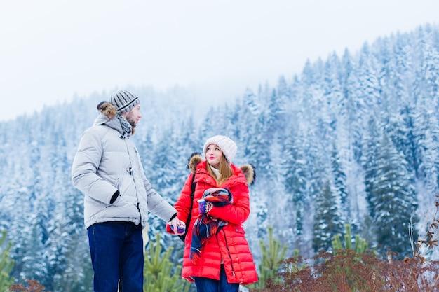 Facet i dziewczyna w zimowych kurtkach i czapkach trzymają się za ręce i patrzą na siebie