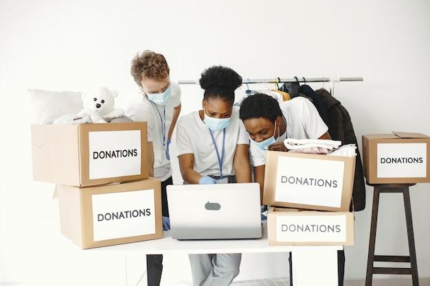 Facet i dziewczyna z polami wyboru wolontariusze w maskach z laptopami pudełka z pomocą humanitarną
