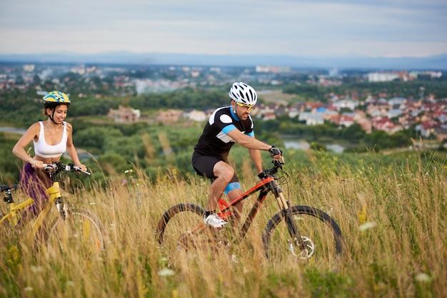 Facet i kobieta na rowerach jeździć na wzgórzu