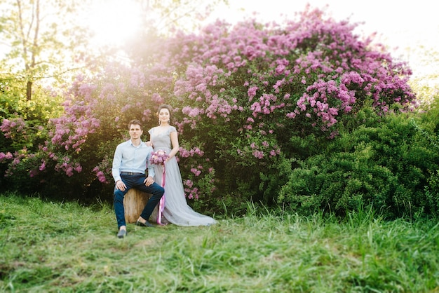 Facet i kobieta spacerują po wiosennym ogrodzie bzu przed ceremonią ślubną