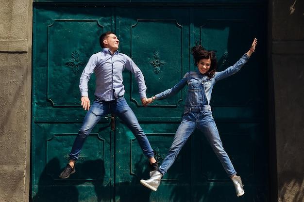 Facet i kobieta trzymają się za ręce i skaczą w pobliże pięknych drzwi