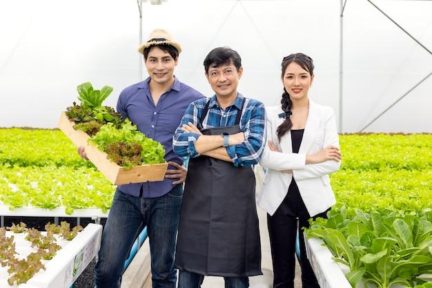 Facet i rolnik obecni na farmie z uśmiechem i dumą z własnego start-upu w hydroponicznej szklarni warzywnej ze szczęściem i radością w tle.