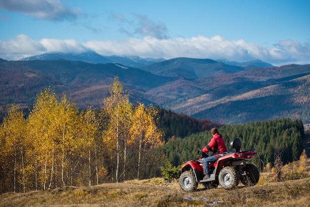 Facet jedzie na atv na pagórkowatej drodze na tle gór, lasów i błękitne niebo na jesieni