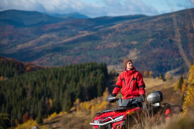 Facet jedzie na quadzie w górach