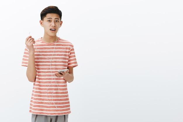 Facet jest rozproszony podczas słuchania muzyki w słuchawkach, zdejmując jedną słuchawkę i wyglądający na zapytanego z otwartymi ustami, jakby zadawał pytanie