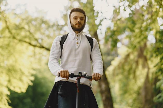 Facet jeździ skuterem elektrycznym w letnim pforest