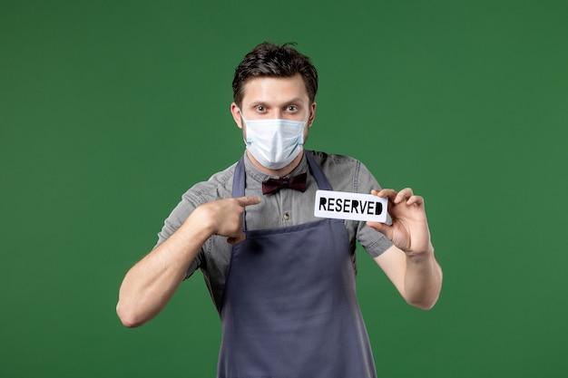 Facet kelner w mundurze z maską medyczną i trzymający zarezerwowaną ikonę na zielonym tle