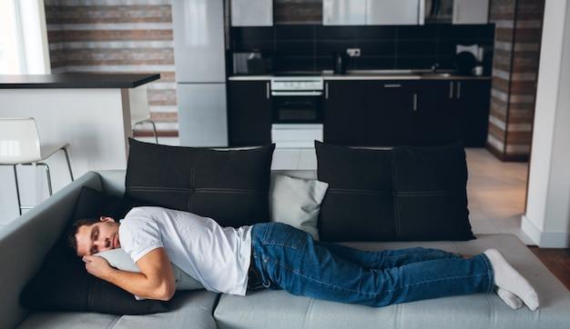 Facet leżący w pozycji poziomej na kanapie. marzyć ze słodkimi snami. odpoczynek i relaks. spokojny spokojny człowiek zmęczony.