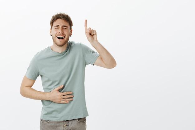 Facet lubi kobiety z poczuciem humoru. portret przystojny zabawny model męski w swobodnej koszulce, śmiejąc się głośno z zamkniętymi oczami i szerokim uśmiechem