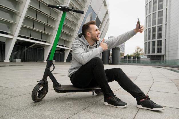 Facet lubi nową wypożyczalnię skuterów elektrycznych. prowadzi rozmowy wideo ze znajomymi i opowiada o zaletach tej aplikacji na smartfony. mężczyzna siedzi na hulajnodze elektrycznej, robi selfie i podnosi kciuki.