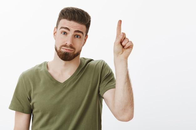 Facet ma jedną sugestię, podnosząc palec wskazujący, dodając pomysł, stojąc głupio i uroczo z niezdecydowanym i nieśmiałym wyrazem twarzy, wydymając pochyloną głowę i patrząc z uroczym uśmiechem, wskazując na białą ścianę