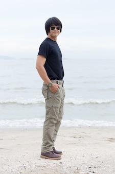 Facet ma na sobie spodnie cargo i stojąc na plaży